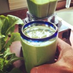 Glass filled with green spinach smoothie.