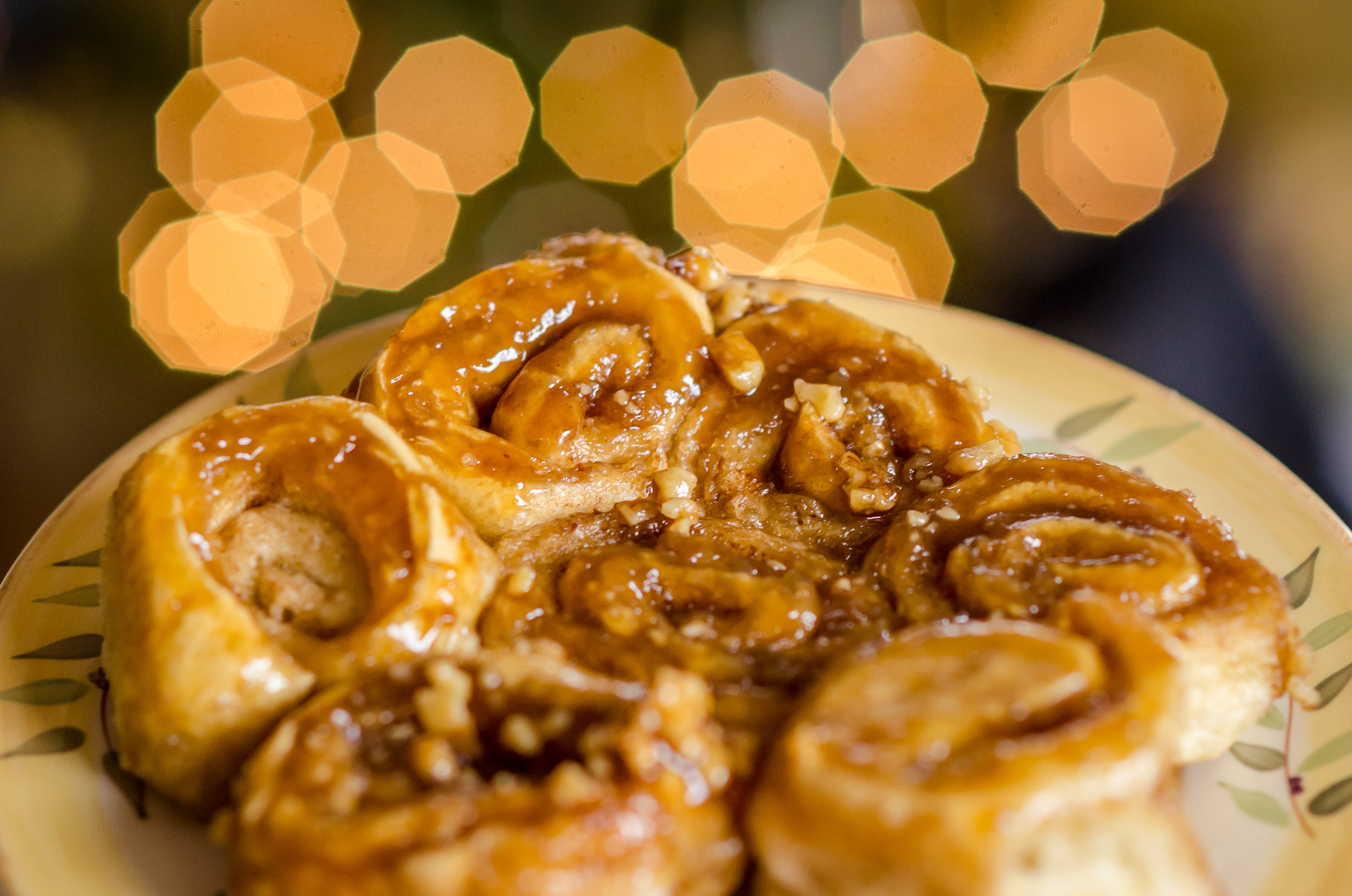 Sticky Buns On A Plate With Lights In The Background