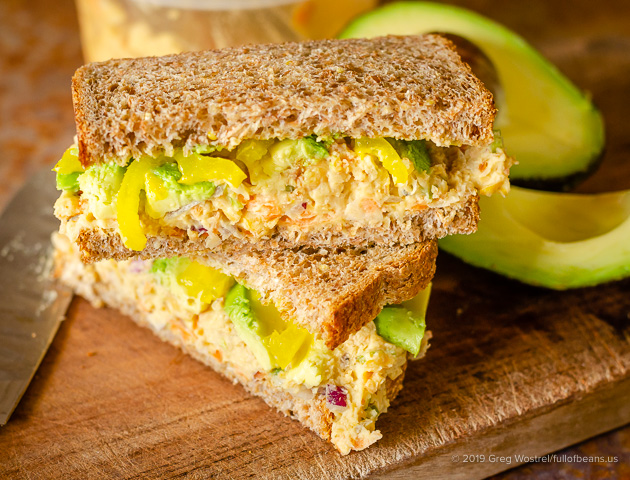 Better Than Tuna vegan chickpea salad in a sandwich with avocados on the side