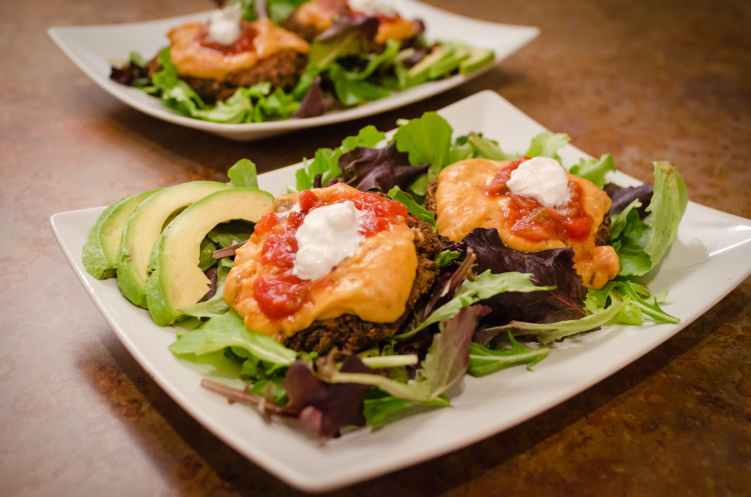 Black bean burger on a plate of greens with cheese sauce, salsa and sour cream