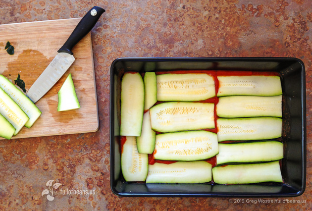Pan of lasagna being assembled showing the zucchini layers that make the vegan zucchini lasagna
