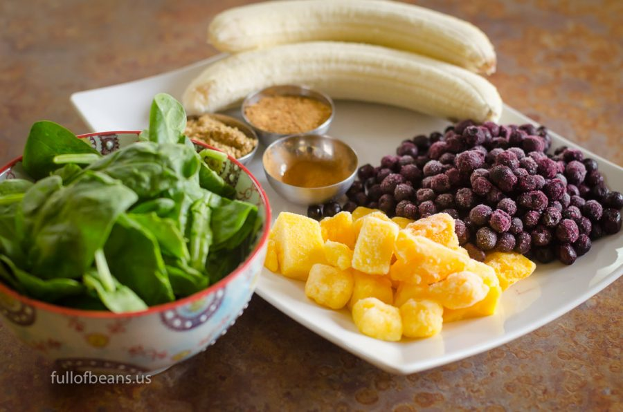 The essential ingredients: fresh baby spinach, bananas, frozen blueberries and mango, cinnamon, flax, and coconut sugar.